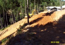 During: Heavy equipment and laborers work to restore natural drainage patterns on the property