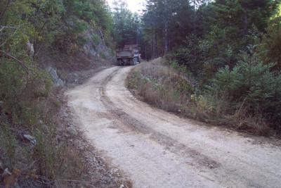 Before: Forest logging road traverses a steep, wet swale showing signs of slope instability