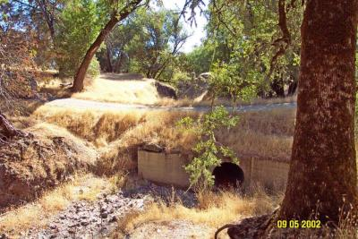 "Before: This ""new"" stream crossing culvert was undersized and prone to plugging and overtopping during high flows."