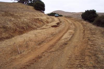 Before: Note the deep wheel ruts and the gully erosion leading to the inboard ditch of this insloped road reach.